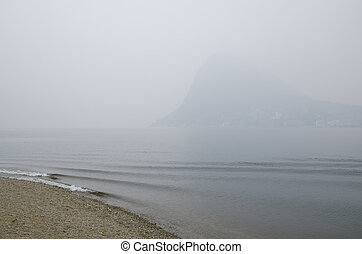 Beach on a foggy lake with mountain