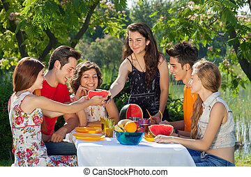 Outdoors pleasure. Happy people at a park enjoying a picnic
