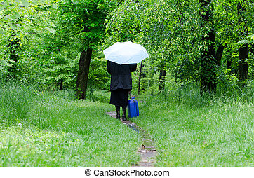 Woman with a umbrella on a green path