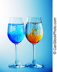 ink in glasses - Two wine glasses filled with water and...