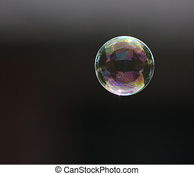 Single bubble - A single bubble floating over a dark...