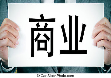 business written in chinese - a man wearing a suit holding a...