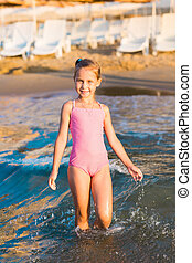 Adorable little girl playing in the sea on a beach -...