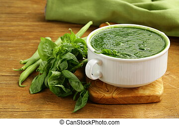 green cream soup of spinach and green peas in white bowl