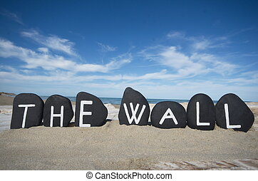 The wall, conceptual black stones composition on the sand