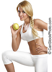 young happy beautiful girl eating a green apple on white