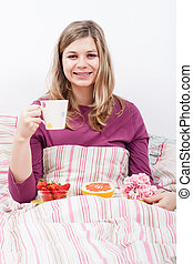 Happy woman with cup of coffee and breakfast
