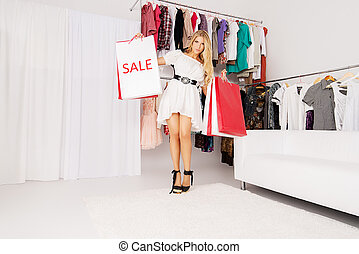 in a store - Fashionable lady standing with a lot of...