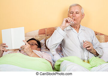 Senior couple relaxing in bed - Retired couple relaxing in...