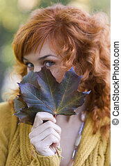 fall leaf - close up of red-haired woman behind a leaf in...