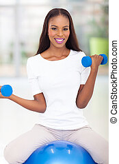 healthy african american woman exercising with dumbbells
