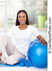 african american woman with exercise ball at home - happy...