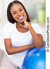african american woman resting on fitness ball - smiling...