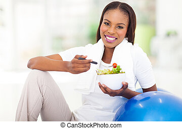 young african woman eating vegetable green salad - beautiful...