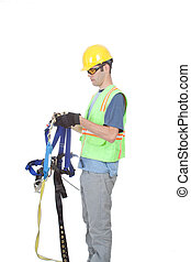 Man Putting on Climbing Harness - A construction worker puts...