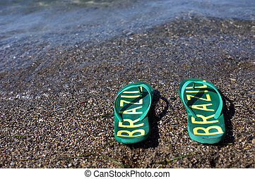 Flip flops on the beach - A pair of green flip flops with...
