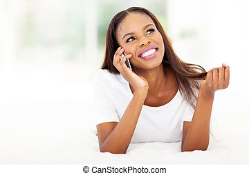 young african woman talking on cell phone - happy young...
