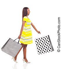 afro american woman walking with shopping bags - side view...
