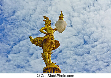 gold kinnaree statue with lantern