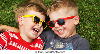 Smiling brothers wearing fancy sunglasses - Smiling young...
