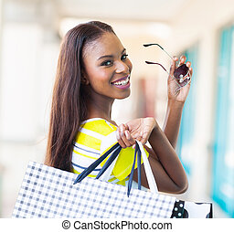 happy african shopper - happy attractive african shopper in...