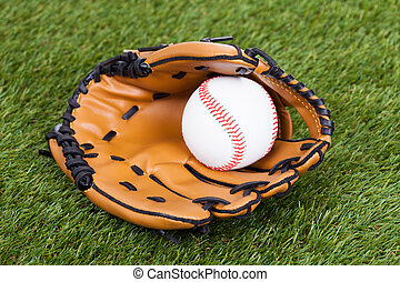 Leather Glove With Baseball Ball On Green Pitch