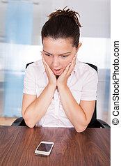 Businesswoman Looking At Cracked Smartphone Placed On Table...