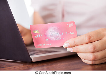 Female Holding Credit Card Over Keyboard - Close-up Of...