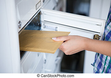 Womans hand pulling envelop from mailbox - Close-up of...