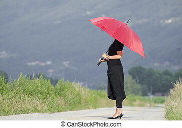 Woman standing on an empty road with a red umbrella