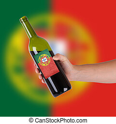 Hand holding a bottle of red wine, label of Portugal,...
