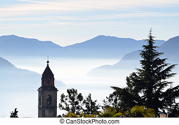 Church close to a lake with fog and mountains - Church tower...