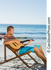 Focused handsome man strumming guitar on the beach