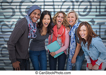 Happy group of friends laughing together on graffiti...