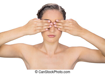 Unsmiling woman hiding her eyes on white background