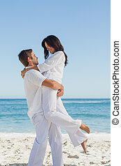 Happy man holding woman in arms against ocean on holidays
