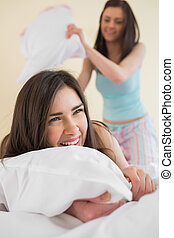Cheerful friends in pajamas having a pillow fight on bed in...