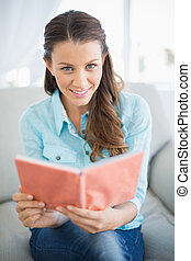 Smiling woman sitting on sofa read - Smiling woman sitting...