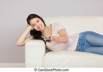 Cheerful asian girl lying on the couch watching tv at home...