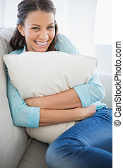 Smiling woman holding pillow sitting on couch in bright...