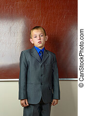 Portrait of schoolboy in classroom standing near the...