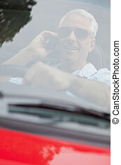 Cheerful handsome man in red convertible having phone call...