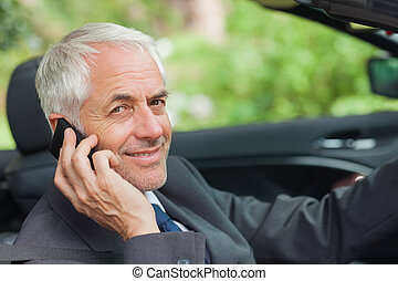 Cheerful businessman on the phone driving expensive...
