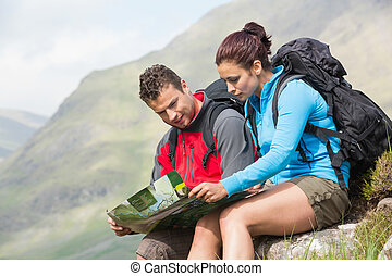 Couple resting after hiking uphill and reading map in the...