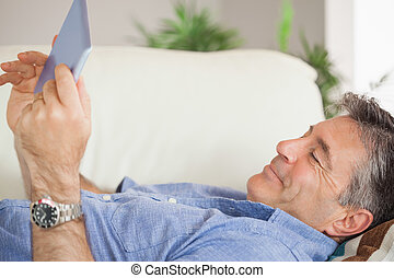 Smiling man laying on a sofa using a tablet pc - Smiling...