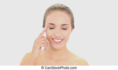 Beautiful model putting face cream on on white background