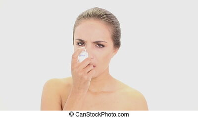 Beautiful model using her asthma inhaler on white background