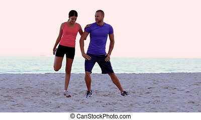 Woman stretching and being coached on the beach on the sand