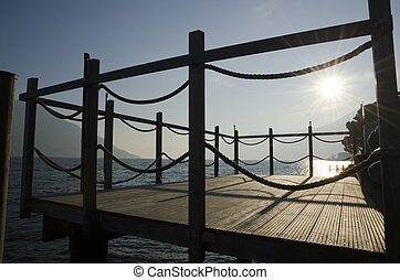 Pier in backlight on a lake with mountain