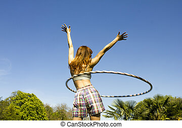 Young woman with hoola hoop in park